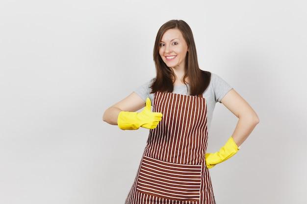 Ama de casa caucásica sonriente atractiva joven en delantal rayado, guantes amarillos aislados. hermosa mujer ama de llaves mostrando el pulgar hacia arriba