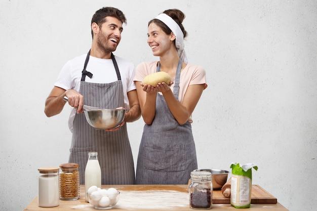 El ama de casa contenta se siente orgullosa, sostiene una masa bien hecha, se la muestra al esposo y va a continuar horneando panecillos.