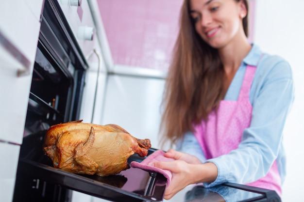 Ama de casa en delantal cocinando pollo entero en el horno para cenar en la cocina