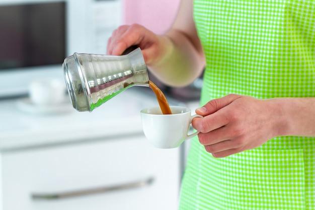 Ama de casa en delantal preparando café turco sabroso caliente de cezve para el desayuno