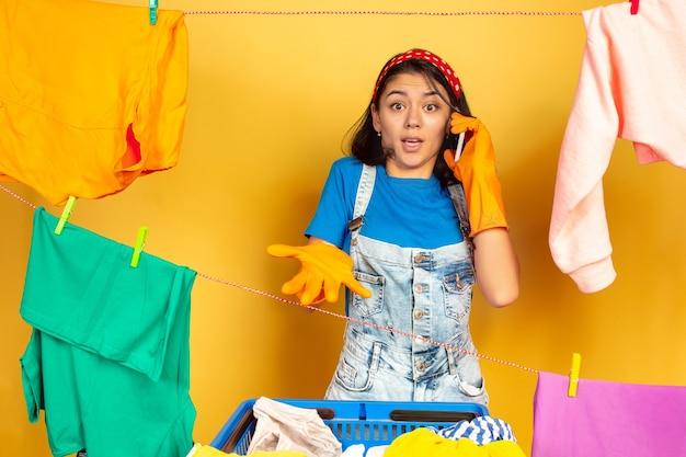 Ama de casa divertida y hermosa haciendo quehaceres domésticos aislados en el espacio amarillo. joven mujer caucásica rodeada de ropa lavada