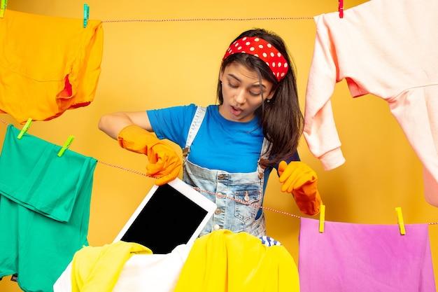 Ama de casa divertida y hermosa que hace las tareas domésticas aisladas sobre fondo amarillo. mujer caucásica joven rodeada de ropa lavada. vida doméstica, obras de arte brillantes, concepto de limpieza. se ha lavado la tableta.