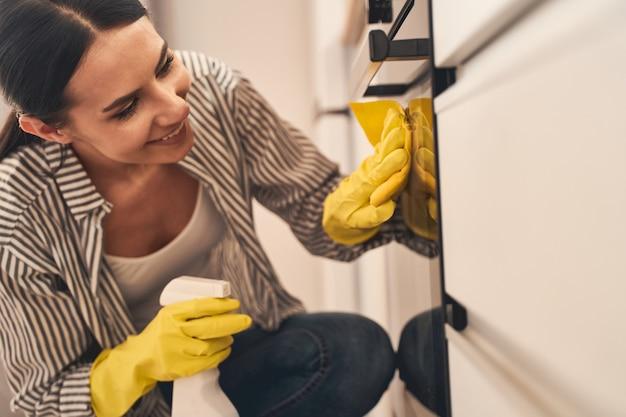 Ama de casa encantada positiva manteniendo una sonrisa en su rostro mientras cuida sus electrodomésticos
