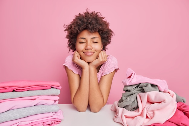 Ama de casa de ensueño complacida se inclina a la mesa con pilas de ropa limpia, mantiene las manos debajo de la barbilla, los ojos cerrados, toma un descanso después de doblar la ropa aislada sobre la pared rosa. concepto de quehaceres domésticos