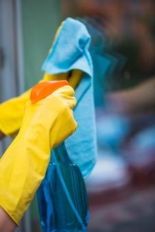 Ama de casa fumigación detergente con botella de spray en la ventana de vidrio