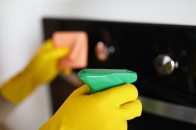 Ama de casa en guantes de goma amarillos soplando spray de limpiador químico en la estufa closeup