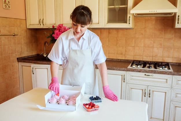 Ama de casa guapa está decorando cupcakes rosas con bayas frescas en el interior de su cocina