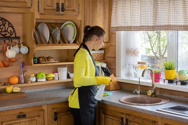 Ama de casa hermosa joven en guantes protectores de goma amarillos que limpian la casa, frota el polvo, lava la encimera de la cocina con un limpiador en aerosol. estilo de vida, servicio de limpieza de tareas domésticas, concepto de limpieza