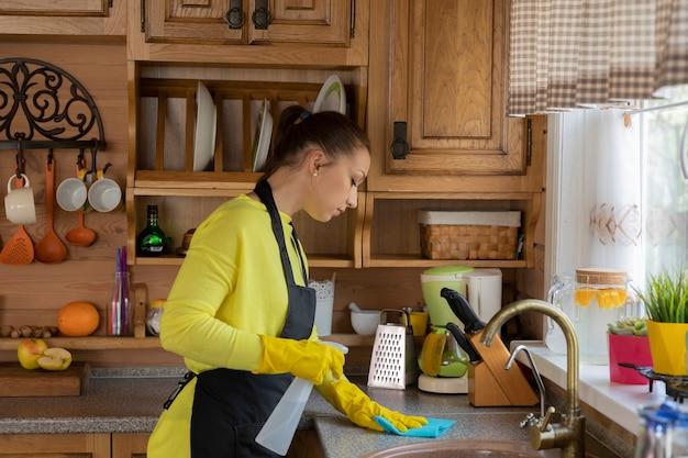 Ama de casa hermosa joven en guantes protectores de goma amarillos que limpian la casa