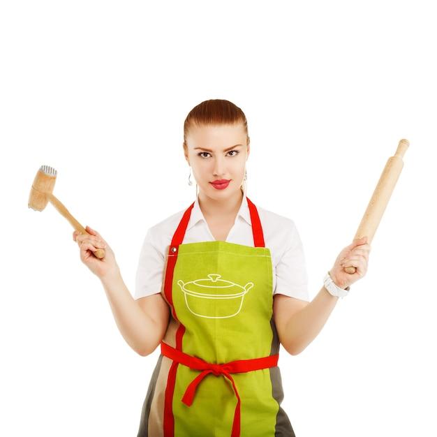 Ama de casa joven y bonita con un rodillo y un martillo de carne en sus manos