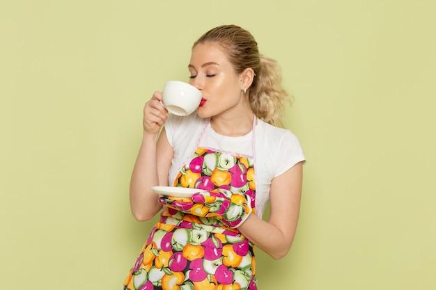 Ama de casa joven en camisa y capa de color bebiendo té en verde