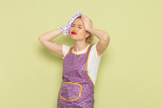 Ama de casa joven en camisa y capa púrpura deprimida en verde