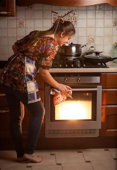 Ama de casa joven control de plato de cocción en el horno