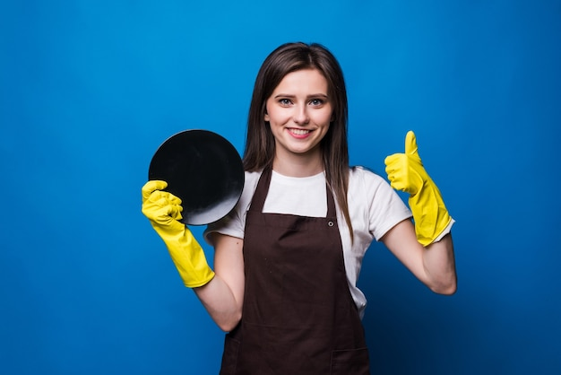 Ama de casa joven en guantes mostrando esponja y plato limpio aislado