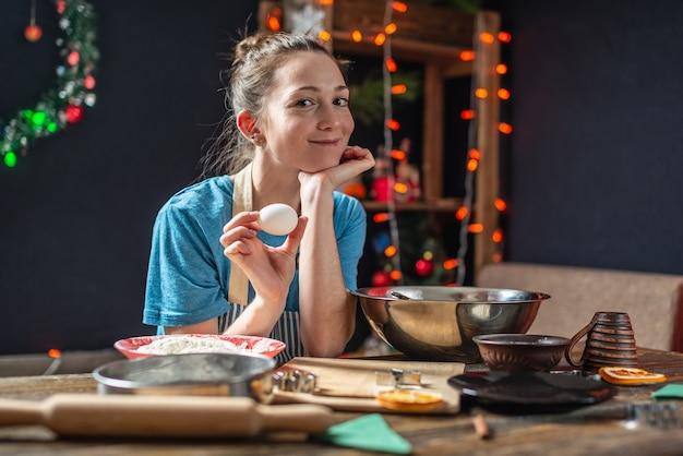 Ama de casa joven hace masa para cocinar galletas de jengibre festivas