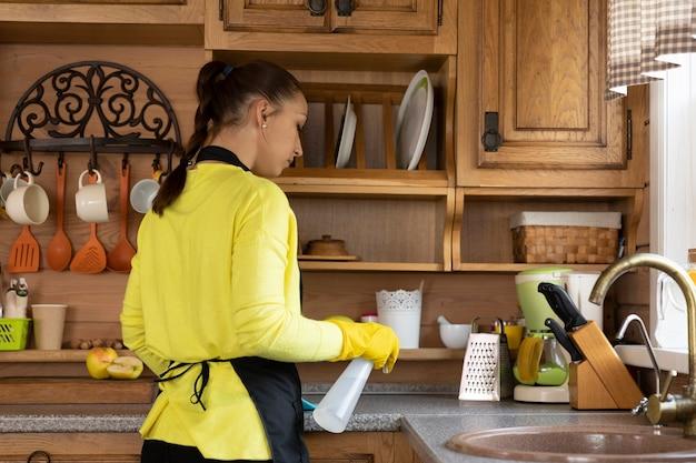 Ama de casa joven linda mujer en delantal protector limpieza casa