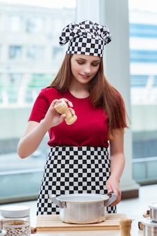 Ama de casa joven que prepara la sopa en cocina