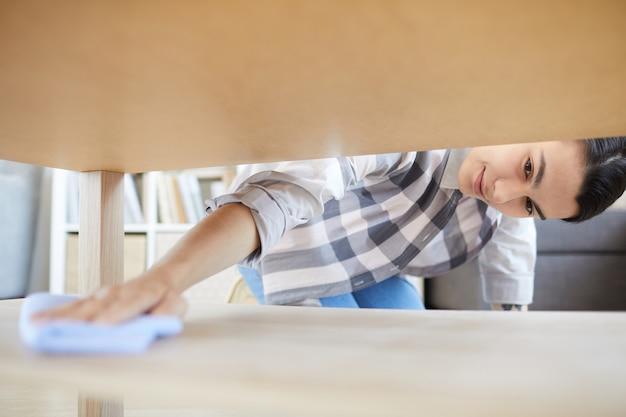 Ama de casa joven que usa un trapo para limpiar el polvo debajo de la mesa en la habitación en casa que ella hace las tareas del hogar