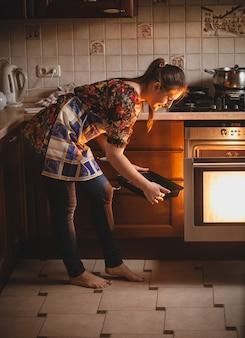Ama de casa joven sosteniendo galletas en la sartén cerca del horno