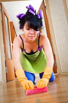 Ama de casa lava un piso en la casa