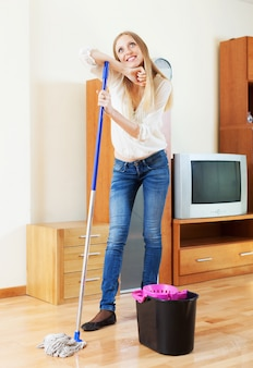 Ama de casa lavando piso de parquet con fregona en casa
