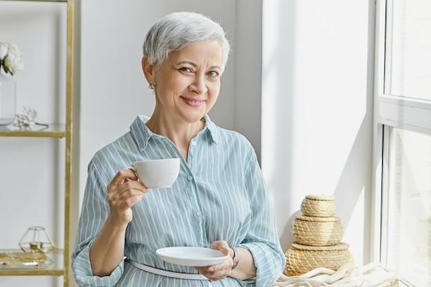 Ama de casa madura de pelo gris elegante atractiva con elegante vestido azul, de pie junto a la ventana con una taza de café mientras almuerza o desayuna. concepto de personas, estilo de vida y hospitalidad