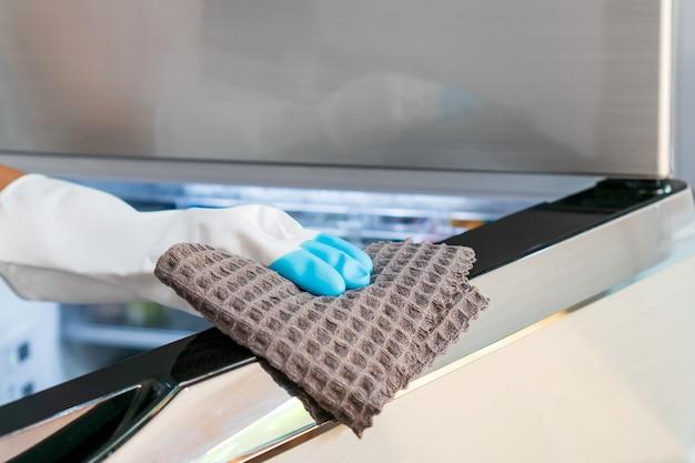 Ama de casa las manos en un guante de goma con un paño de microfibra limpiando una superficie de nevera en la cocina de casa