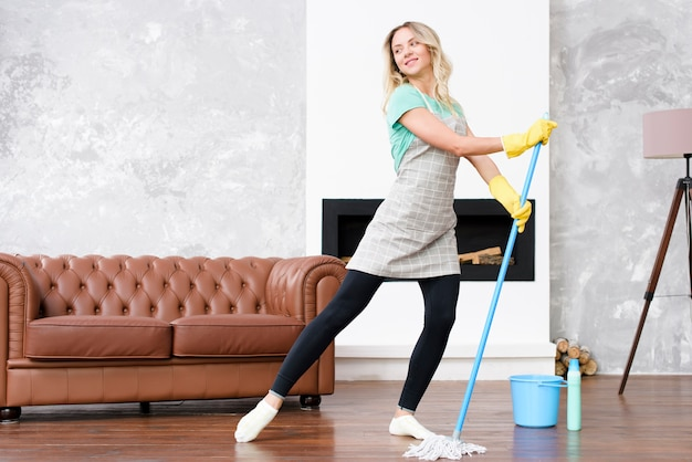 Ama de casa mujer vistiendo delantal bailando con un trapeador mientras realiza las tareas domésticas