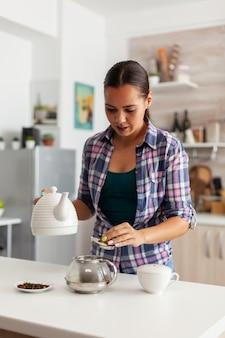 Ama de casa preparando drinkg caliente en la cocina con hierbas aromáticas en la tetera