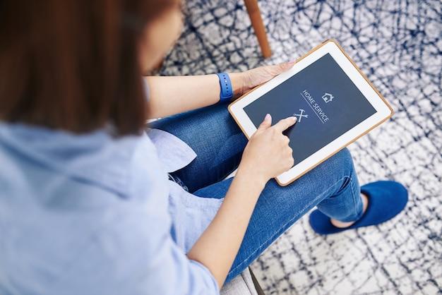 Ama de casa que usa la aplicación de servicio a domicilio en una tableta para comunicarse con el plomero o el personal de mantenimiento