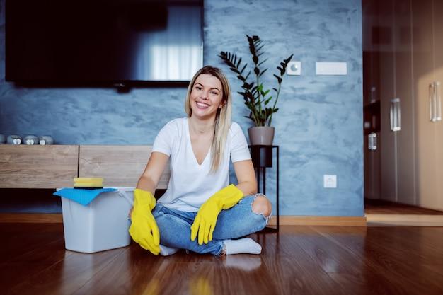 Ama de casa rubia sonriente caucásica atractiva joven con los guantes de goma en las manos que se sientan en el piso con las piernas cruzadas y que miran. junto a ella hay un cubo.