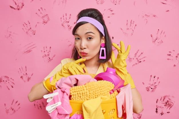 Ama de casa segura de sí misma posa sobre la pared rosa con huellas de manos