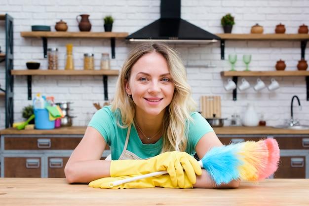 Ama de casa sonriente apoyándose en el mostrador de la cocina con plumero mirando a la cámara