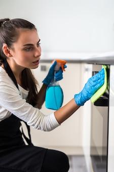 Ama de casa sonriente de la mujer joven que limpia los muebles en cocina