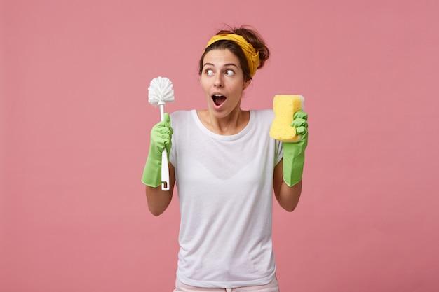 Ama de casa sorprendida en camiseta blanca informal y guantes protectores para limpiar yendo a ordenar la habitación sosteniendo un cepillo con una esponja con mirada perpleja mientras recuerda su reunión con un amigo