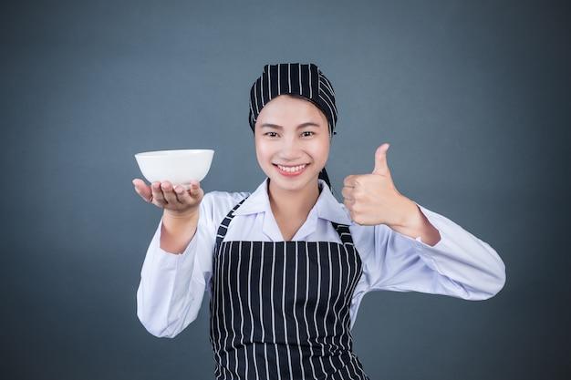 Una ama de casa sosteniendo un plato vacío con comida.