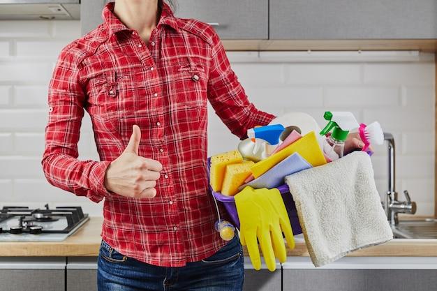 El ama de casa sosteniendo suministros y productos de limpieza en un balde y mostrando ok, firme con el pulgar hacia arriba
