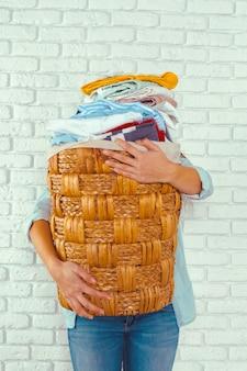 Ama de casa trayendo una gran pila de ropa en la tabla de planchar