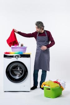 Ama de casa vista frontal en delantal poniendo una toalla en una lavadora sobre fondo blanco.