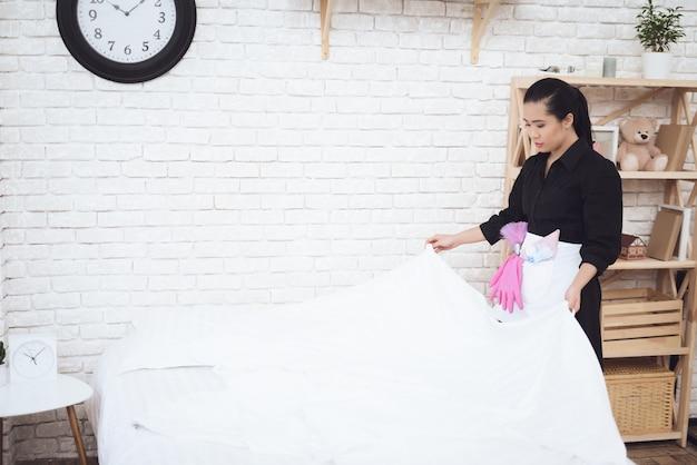 Ama de llaves asiática hace cama en apartamento moderno