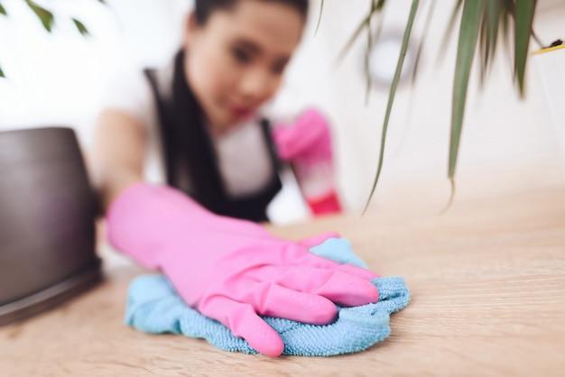 El ama de llaves filipino limpia el polvo de los muebles.