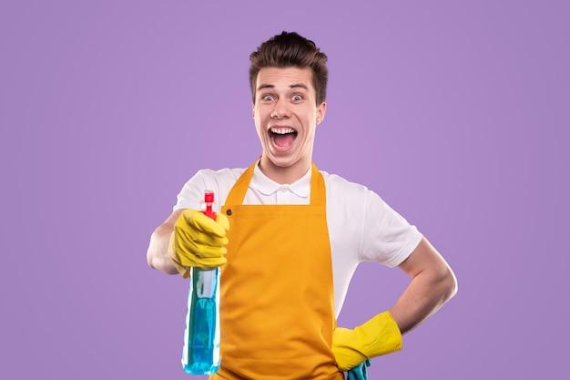 Ama de llaves masculino emocionado mirando a la cámara con la boca abierta y rociando detergente durante la rutina de limpieza contra el fondo violeta