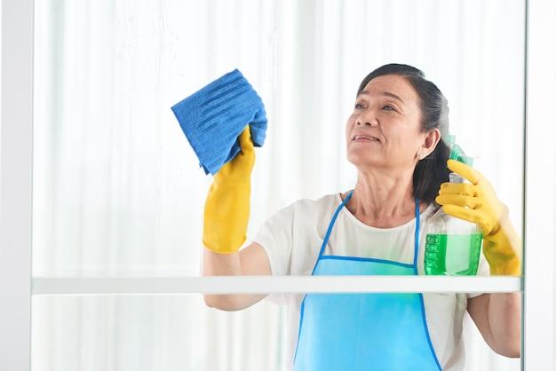 Ama de llaves de mediana edad limpiando la ventana con limpiador en aerosol