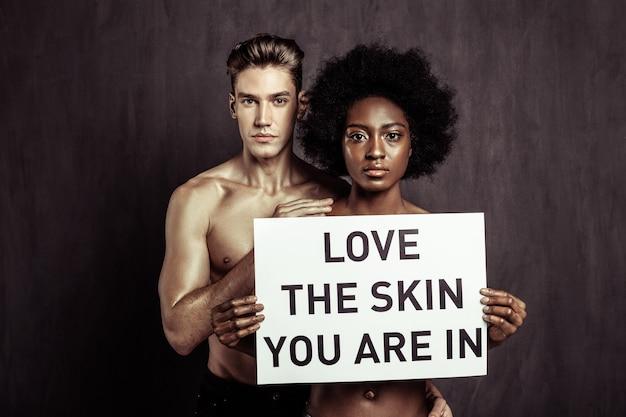 Ama la piel en la que te encuentras. grave mujer afroamericana sosteniendo un cartel con una inscripción mientras participa en la campaña social