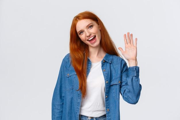 Amable, alegre y extrovertida guapa pelirroja agitando la palma de la mano, saludando