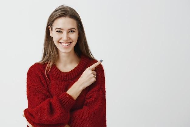 Amable y amable asistente de tienda listo para ayudar a encontrar el camino. retrato de atractiva mujer europea alegre en suéter rojo suelto, apuntando a la esquina superior derecha, sonriendo ampliamente y expresando un estado de ánimo positivo