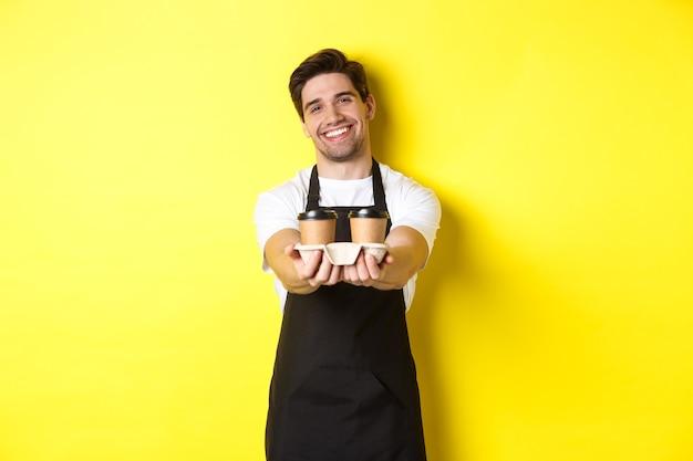 Amable barista en delantal negro dando orden de comida para llevar, sosteniendo dos tazas de café y sonriendo, de pie sobre fondo amarillo