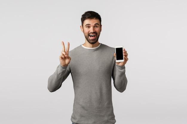 Amable y despreocupado, divertido, hombre gay con barba en suéter gris, edite la foto de perfil de la aplicación de citas en línea, haga el signo de la paz, muestre la pantalla del teléfono inteligente y sonría feliz