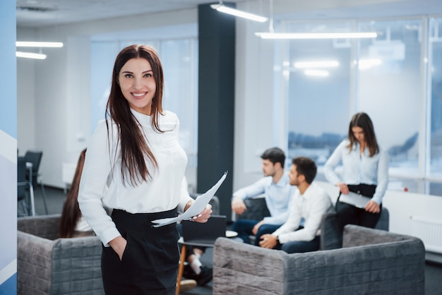 Amable gerente sonriendo a la cámara. retrato de joven se encuentra en la oficina con empleados en el fondo