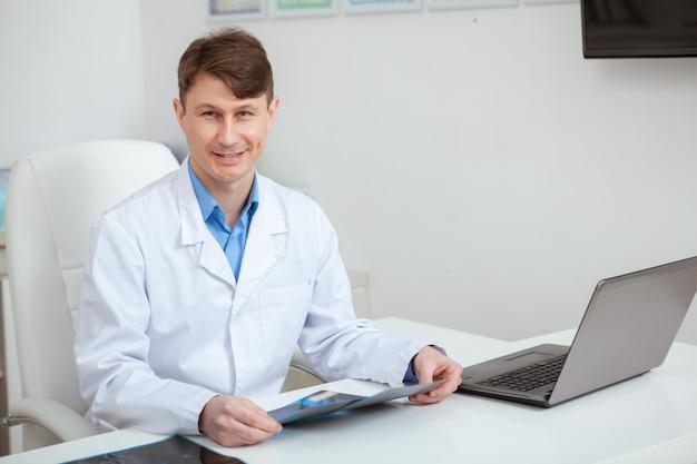 Amable médico varón maduro sonriendo sentado frente a la computadora portátil en su oficina